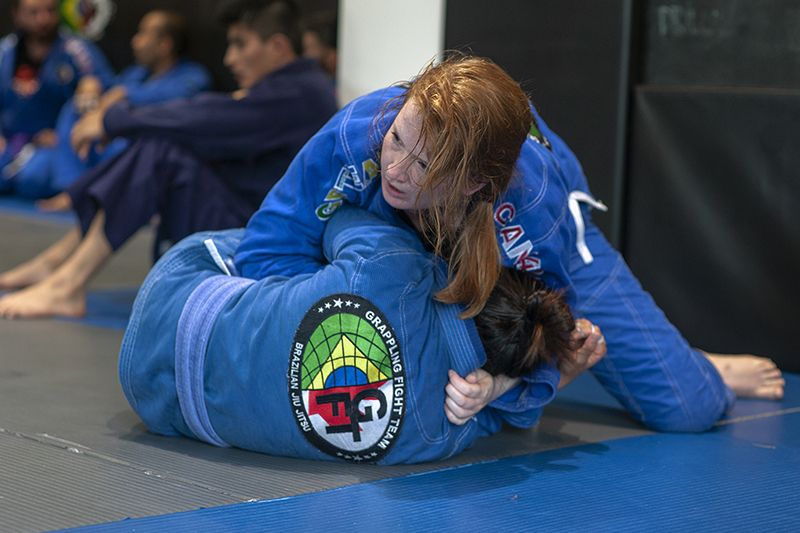 Two women sparring during fundamentals bjj class